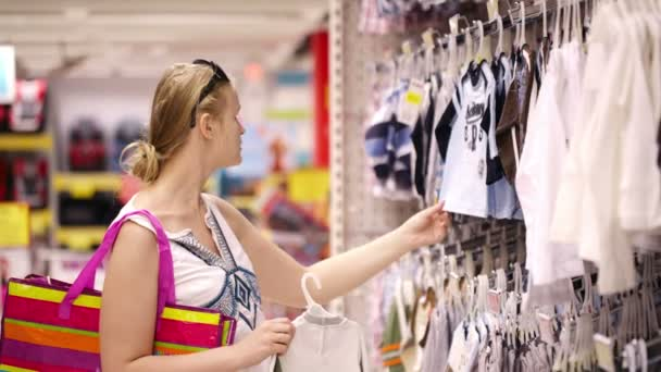 Young mother shopping for childrens clothes
