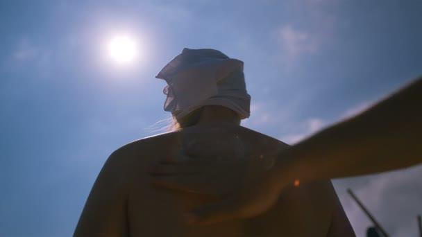 třením opalovací krém na jeho žena mužovo zpět k ochraně proti škodlivému uv záření slunce