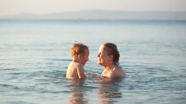 Mother playing with her young son in the sea