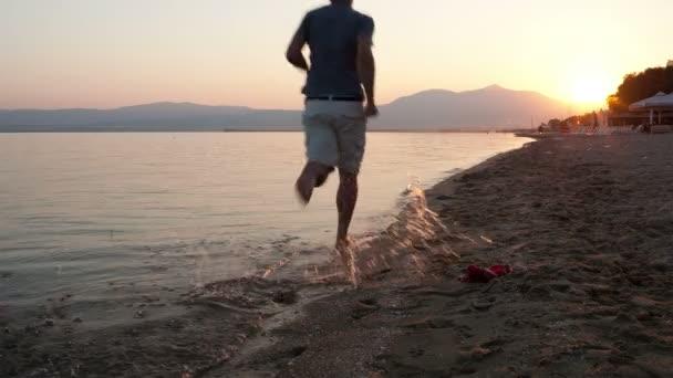 muž běží podél tropická pláž za svítání se sluncem