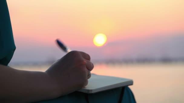 zblízka pohled na straně ženy psát ve svém deníku při západu slunce
