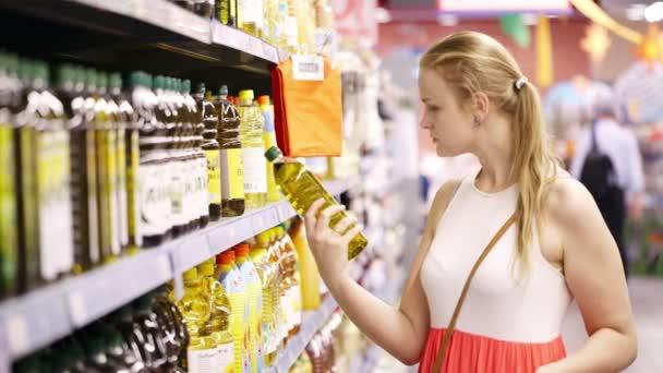 mladá blondýna výdeje láhev olivového oleje
