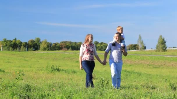 Mother, father and their little son walking in the countryside