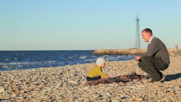 otec a jeho malý syn hraje na oblázkové pláži házel kameny. Rodinná zábava venku