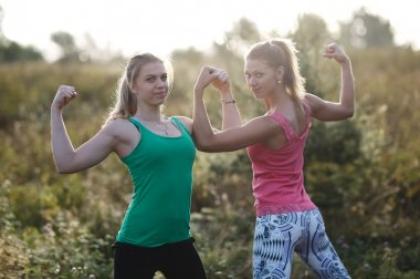 Two athletic girls flexing their arm muscles