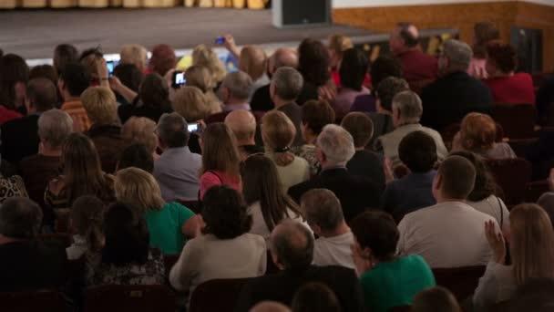 Menschen im Publikum sitzen und applaudieren