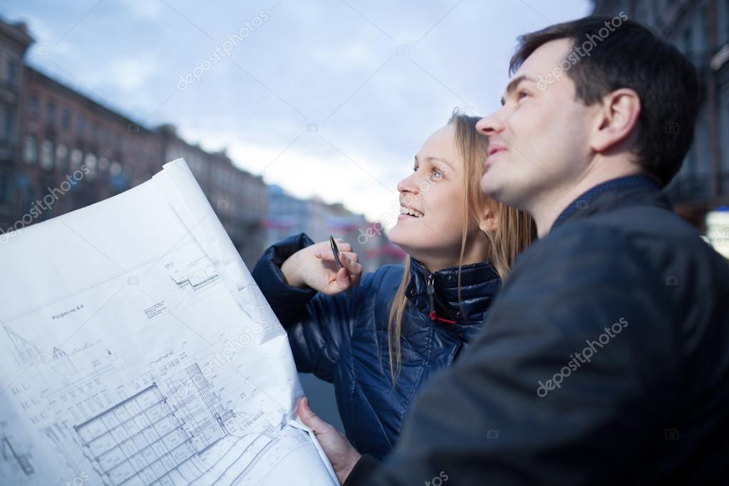 Couple holding blueprints admiring building