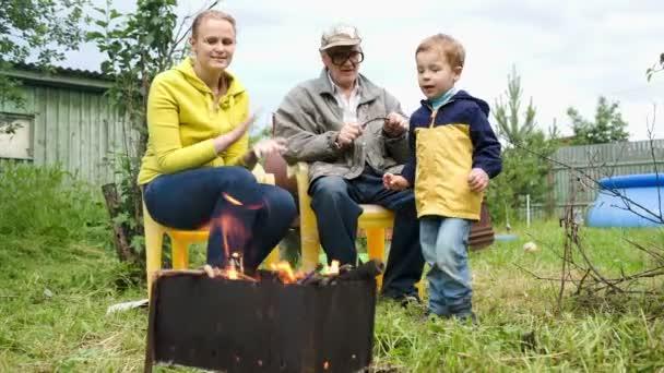 anya, a fia és a nagypapa a tűz, az udvarban