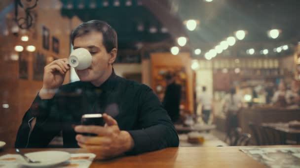 muž pomocí telefonu a mít kávu v kavárně
