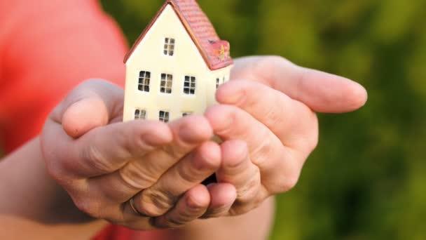 Paar hält ein kleines Spielzeughaus in den Händen