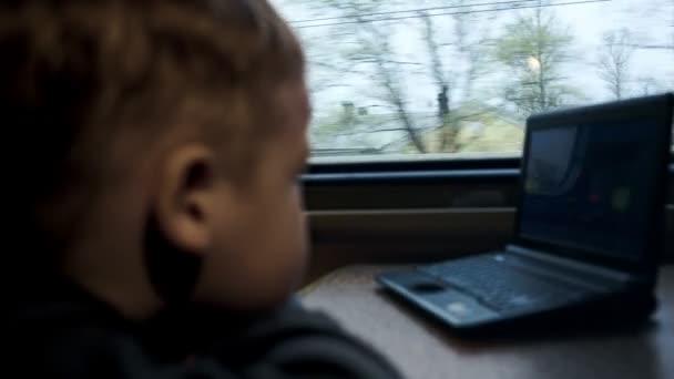 chlapec sledování filmu na notebooku ve vlaku