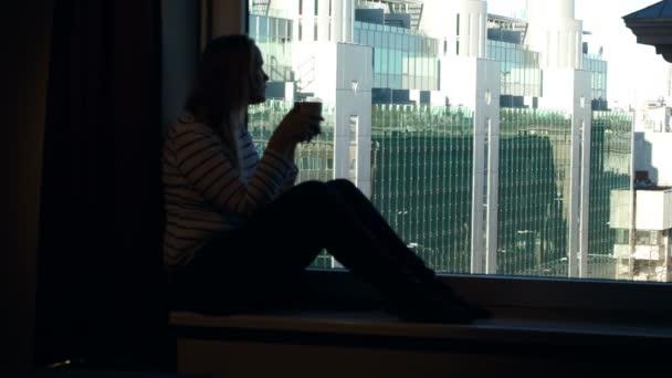 Woman drinking coffee on the windowsill