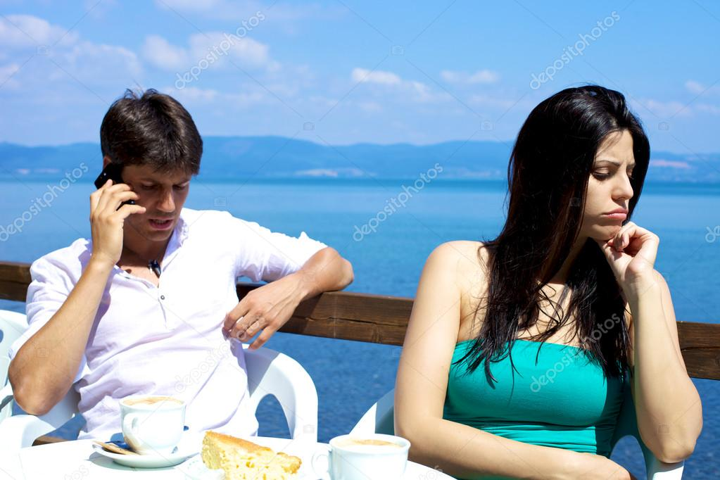 Girlfriend angry with boyfriend on the phone on the lake