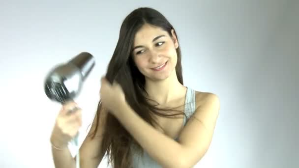 glückliche junge Frau trocknet lange Haare