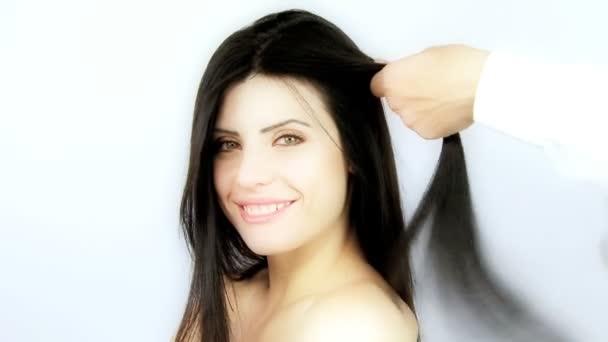 Žena, zatímco kartáčováním a žehlení dlouhou hedvábnou černé vlasy kadeřnictví