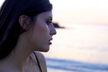 Sad woman crying during sunset