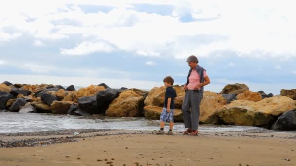 Boy playing with grandmother on the beach