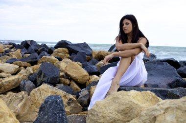 Sad woman sitting on rocks in front of ocean