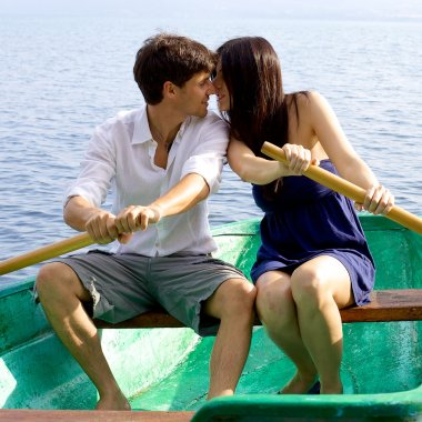 Italian couple on wood boat rowing and kissing