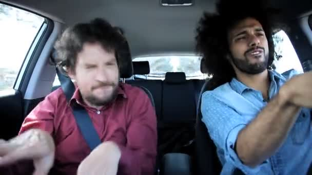 Two friends singing and dancing in car