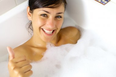 Happy girl taking relaxing bath thumb up