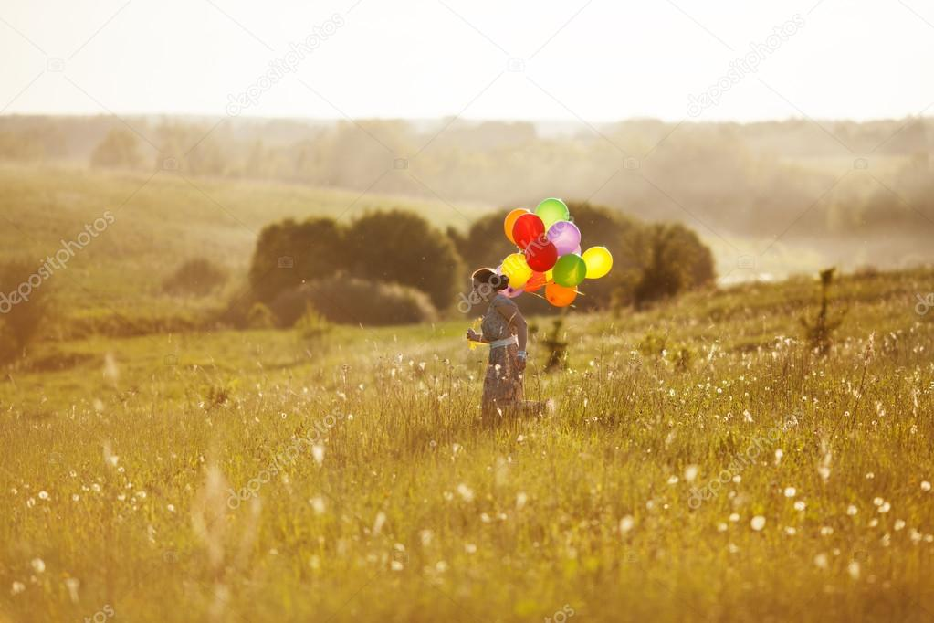 Happy girl with balloons running on the field