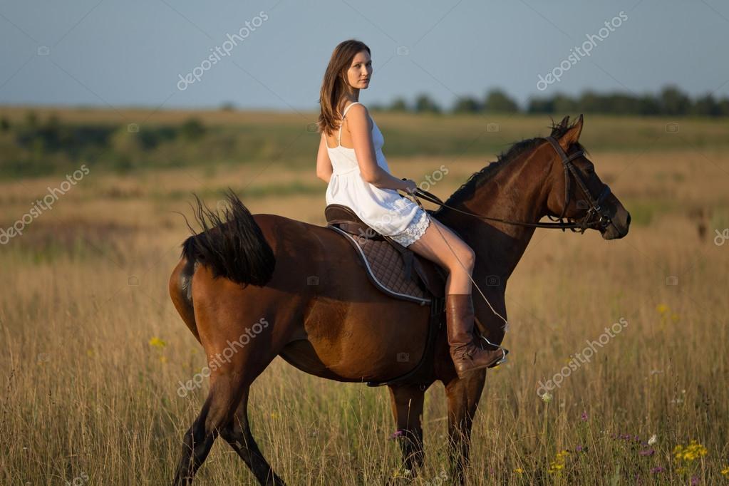 mädchen im weißen kleid auf einem pferd reiten — stockfoto