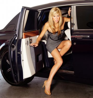 Beautiful young woman exiting a luxury car