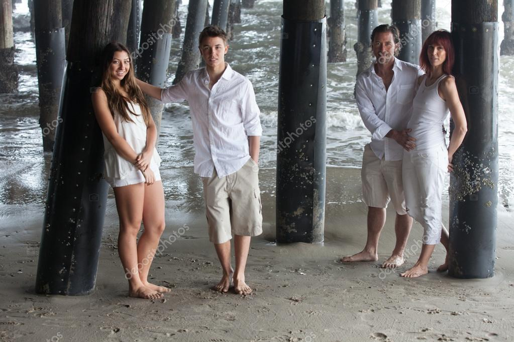 Attractive family posing for a portrait under the santa monica pier in california while on vacation photo by deborahkolb