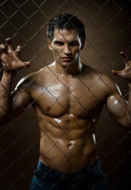 Muscular guy on netting steel fence