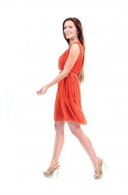 Pretty young female model in dress walking on white background and smiling