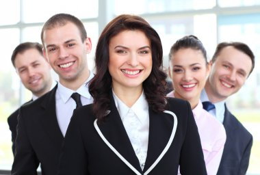 happy young female business leader standing in front of her team