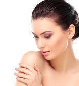 krásná dívka dotýká její tvář. izolované na bílém pozadí. perfektní pleť. krása tváře. profesionální make-up
