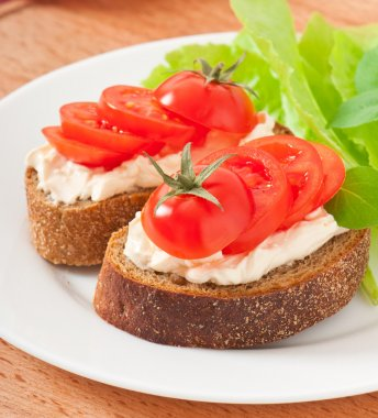 Warm bread tomatoes, cream cheese and basil