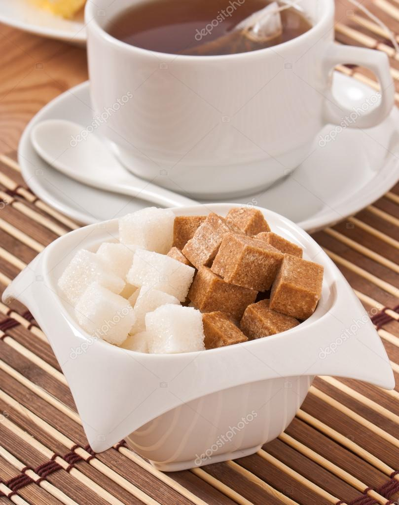 Cubes of white and brown sugar and a cup of tea