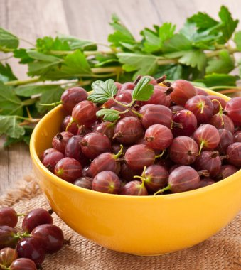 Red gooseberries in a yellow bowl