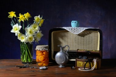 Bouquet of flowers in a vase and an old radio on the table