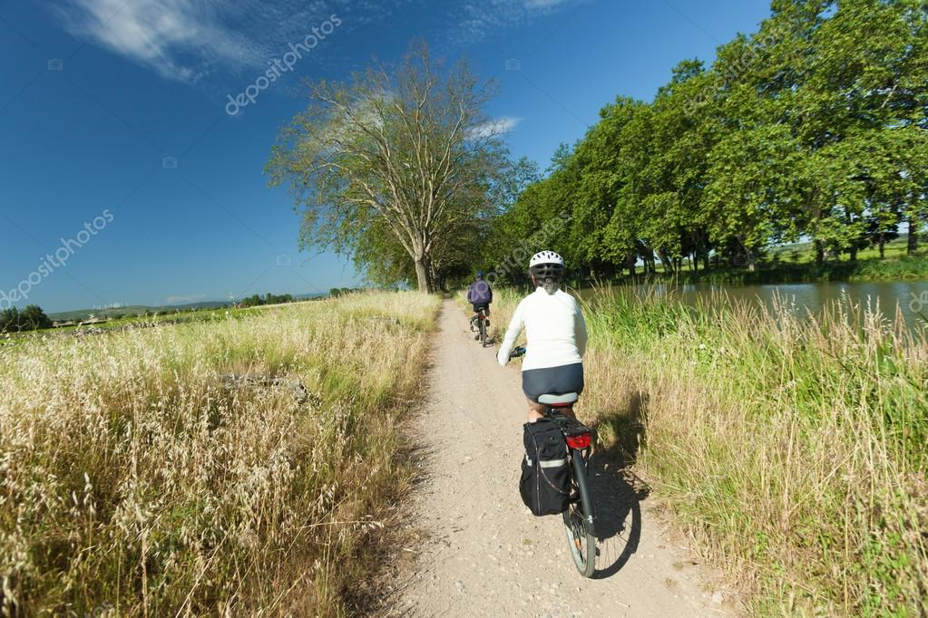 Woman and man cycling on path near river on the canal du midi in France.
