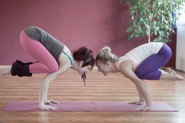 Two young woman practicing yoga