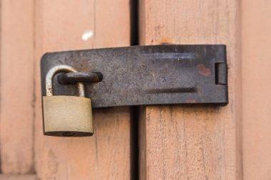 Old wooden doors locked by rusty padlock.