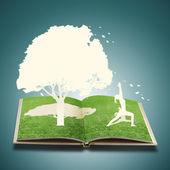Fotografia carta tagliata della ragazza yoga sulla vecchia erba libro