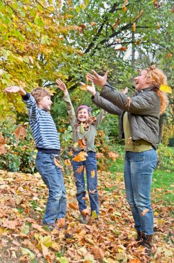 Happy family in autumn forest play with fallen leaf