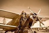 Fotografia Ritratto di bella donna pilota con aereo dietro