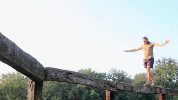 equilibrist walking on a wooden fence