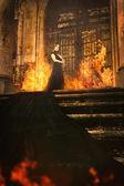 Frau neben altem brennenden Schloss in Stoff