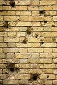 díry po kulkách v cihlové zdi