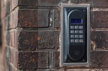 Old intercom on a red brick wall