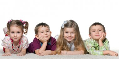 Four children lying on the carpet