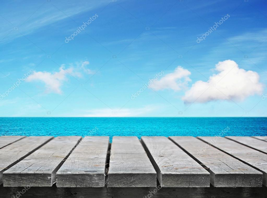 Wooden table on sunny day near sea