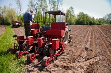 Farmer filling sower to work lands with tractor